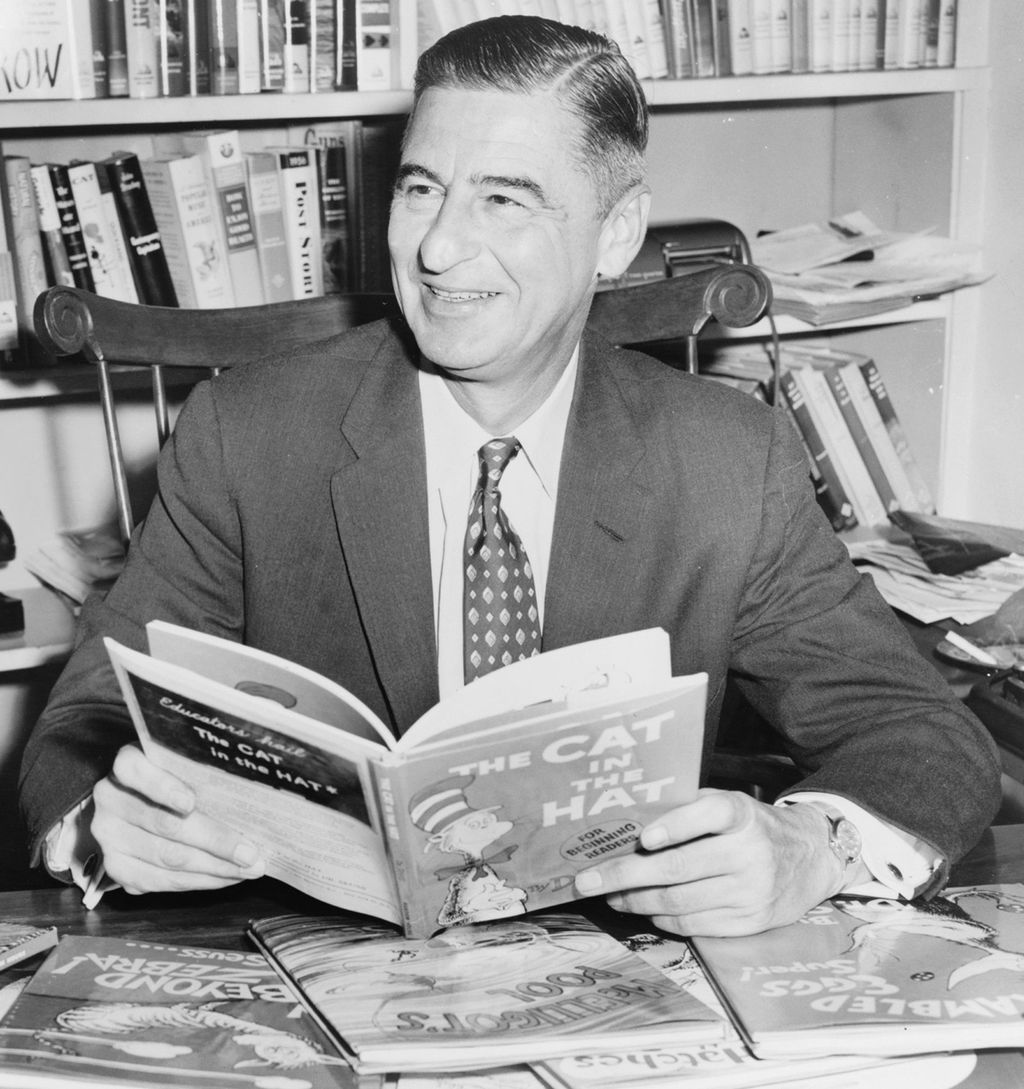 "old photo of Dr. Suess holding the book he wrote entitle ""The Cat In the Hat"""